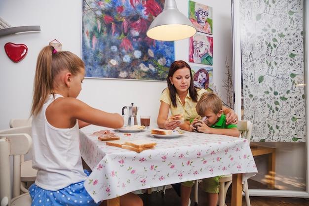 Rodzina siedzi przy stole o śniadanie