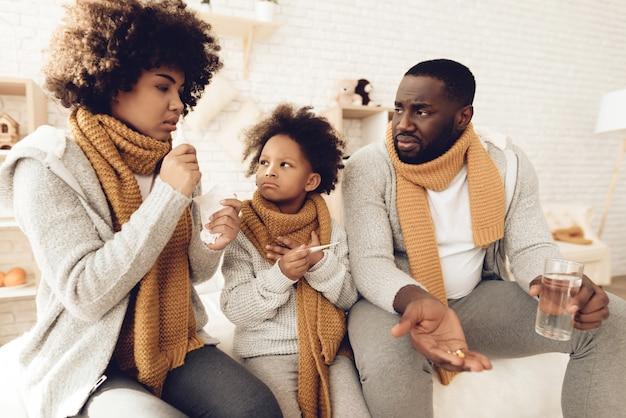 Rodzina siedzi w domu i ma przeziębienie.