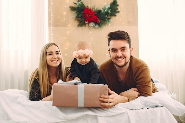 Rodzina siedzi w domu na łóżku z prezentami