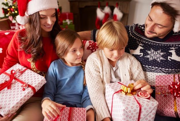 Rodzina siedzi w domu z prezentami świątecznymi