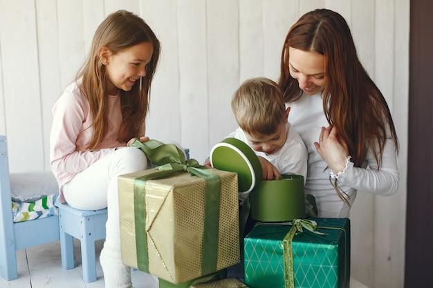 Rodzina siedzi w domu z prezentami
