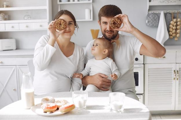Rodzina siedzi w kuchni i je śniadanie