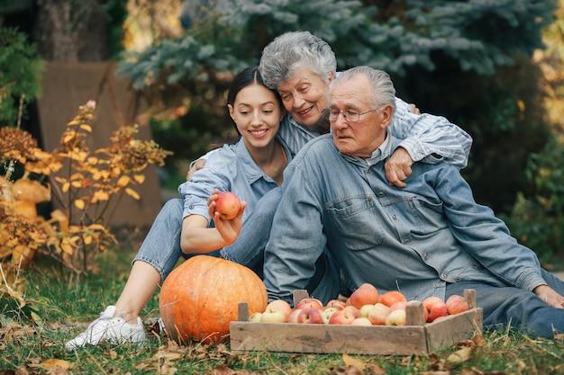Rodzina siedzi w ogrodzie z jabłkami i dyni
