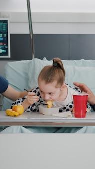 Rodzina siedzi z córką chorą dziewczynę podczas jedzenia zdrowego posiłku żywieniowego