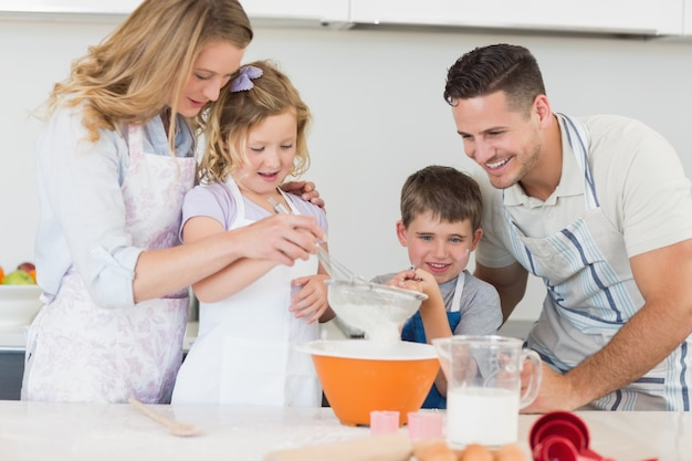 Rodzina składająca się z czterech osób przygotowywa ciastka