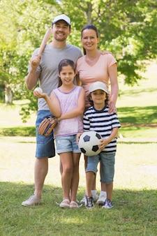 Rodzina składająca się z czterech osób trzyma kij bejsbolowego i piłkę w parku