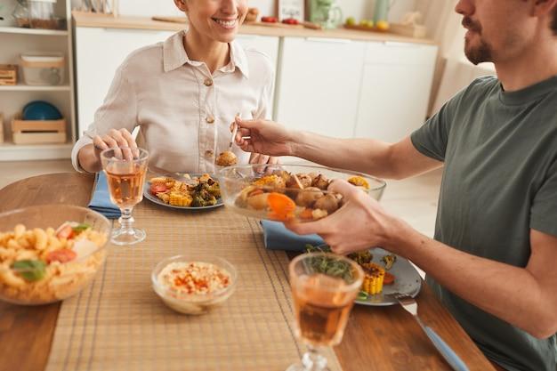 Rodzina składająca się z dwóch osób siedzi przy stole i pije wino w kuchni w domu