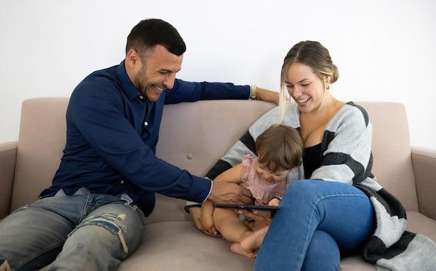 Rodzina śmiejąca się i bawiąca się na kanapie z tabletem