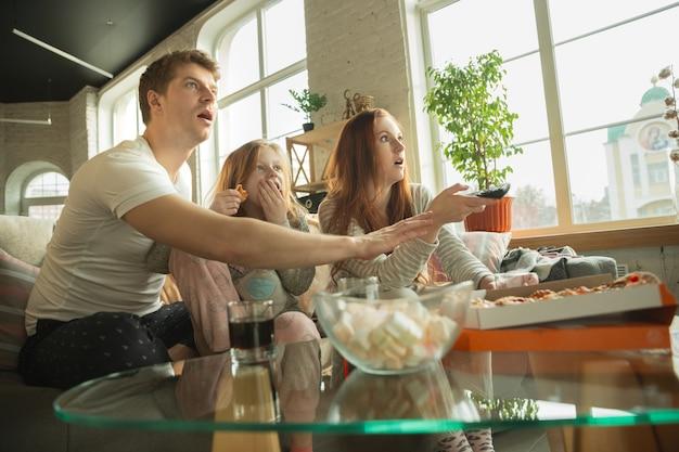 Rodzina spędza miło czas razem w domu, wygląda na szczęśliwą i podekscytowaną, jedząc pizzę, oglądając mecz sportowy