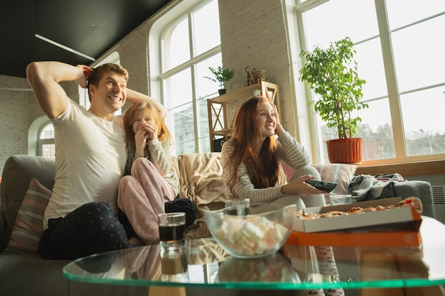 Rodzina spędza miło czas razem w domu, wygląda na szczęśliwą i podekscytowaną. mama, tata i córka bawią się, jedzą pizzę, oglądają mistrzostwa sportowe w telewizji. razem, komfort w domu, koncepcja miłości.
