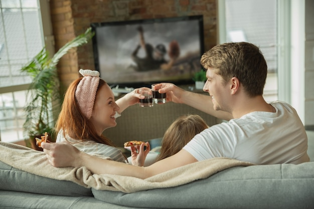 Rodzina spędza miło czas razem w domu, wygląda na szczęśliwą i podekscytowaną. mama, tata i córka bawią się, jedzą pizzę, oglądają mistrzostwa w piłce nożnej w telewizji. razem, komfort w domu, koncepcja miłości.