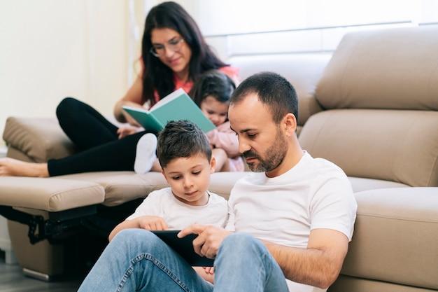 Rodzina spędzająca czas w salonie z technologią