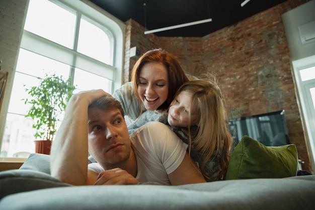 Rodzina spędzająca miło czas razem w domu, wygląda na wesołą i wesołą, leżąc razem
