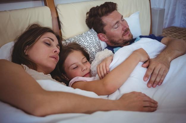 Rodzina śpi na łóżku