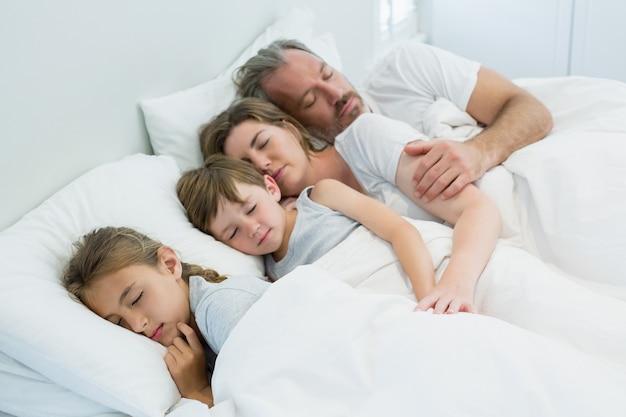 Rodzina śpi razem w łóżku