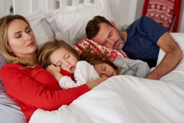 Rodzina śpi w łóżku
