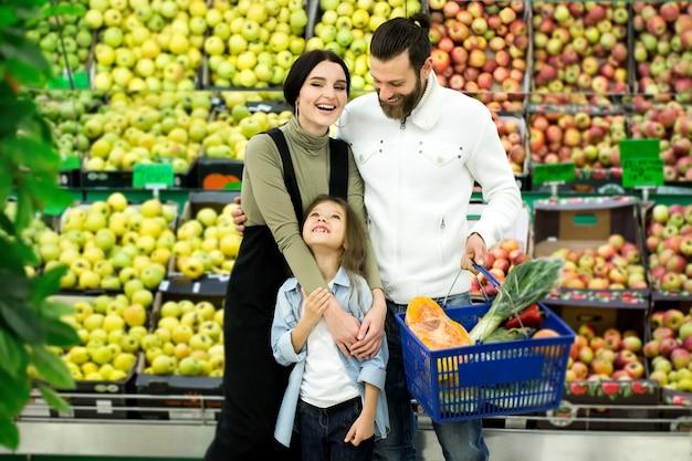 Rodzina stoi z pełnym wózkiem w supermarkecie w dziale warzyw