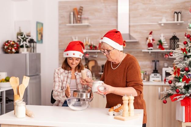 Rodzina świętująca święta bożego narodzenia przygotowująca domowy deser z ciasta