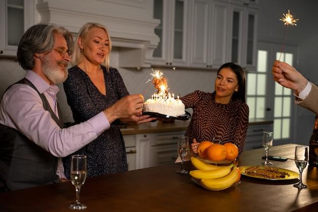Rodzina świętująca urodziny podekscytowanego dziadka, babcia przynosząca tort ze świeczkami