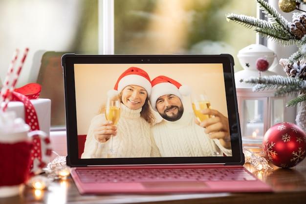 Rodzina świętuje boże narodzenie online przez czat wideo w kwarantannie. koncepcja lockdown zostaje w domu. impreza bożonarodzeniowa podczas pandemii koronawirusa covid 19