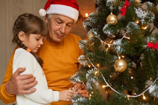 Rodzina świętuje boże narodzenie w domu, dziadek i wnuk wspólnie dekorują choinkę