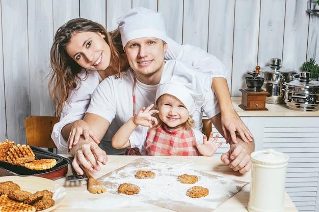 Rodzina, szczęśliwa córka z tatą i mamą w domowej kuchni, śmiejąc się i przygotowując jedzenie razem, z miłością