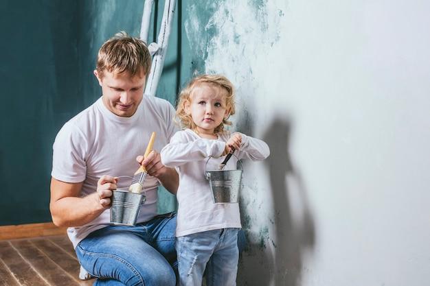 Rodzina, szczęśliwa córka z tatą robi remont domu, maluje ściany, razem z miłością