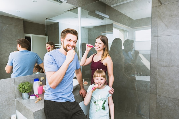 Rodzina szczotkuje zęby w łazience