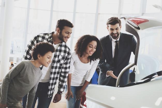 Rodzina szuka w bagażniku samochodu ludzie kupują pojazd.