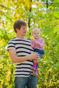 Rodzina tata i córka na spacer w parku jesienią. dziecko jest w bezpiecznych rękach ojca