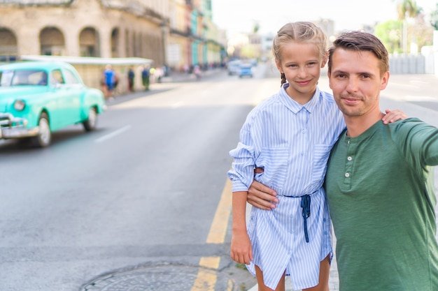 Rodzina tata i mała dziewczynka bierze selfie w popularnym terenie w starym havana, kuba. małe dziecko i młody ojciec na zewnątrz na ulicy w hawanie