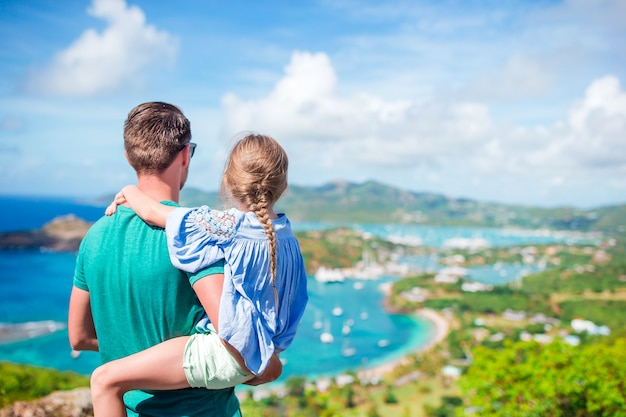 Rodzina tata i małe dziecko, ciesząc się widokiem malowniczego angielskiego portu w antigua na morzu karaibskim
