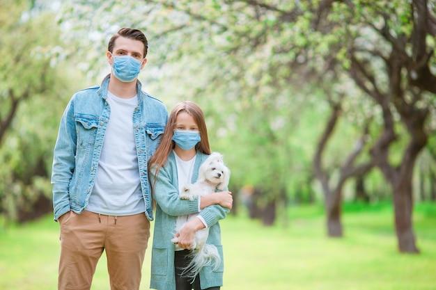 Rodzina taty i dziecka z psem w ochronnej masce medycznej zapobiegającej wirusowi na świeżym powietrzu w parku