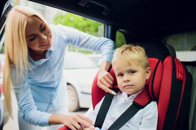 Rodzina, transport, wycieczka samochodowa i ludzie pojęć, - szczęśliwy kobiety uczepienia dziecko z zbawczym pasem bezpieczeństwa w samochodzie