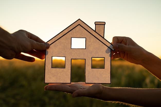 Rodzina trzyma papierowy dom o zachodzie słońca słońce świeci przez okno ręka trzyma wyciętą z papieru symbole domu...