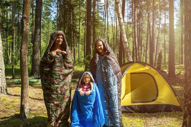 Rodzina turystów od ojca, matki i córeczki pozuje w śpiworach w pobliżu namiotu. rodzinny wypoczynek na świeżym powietrzu, turystyka krajowa, camping, sprzęt turystyczny. przepoczwarzane jak gąsienice-humor
