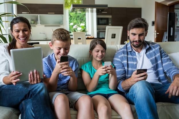 Rodzina używa laptop i telefon komórkowego w żywym pokoju