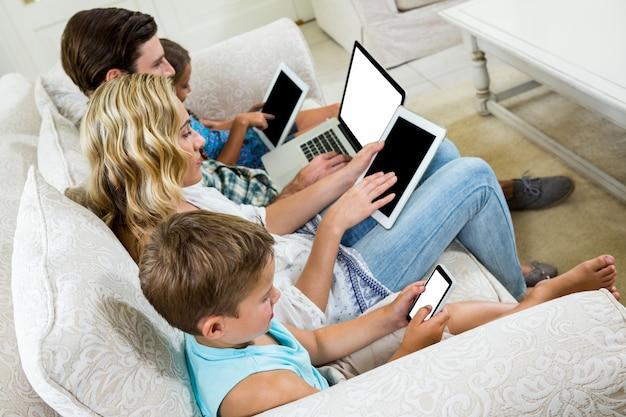 Rodzina używa różnorodne technologie podczas gdy siedzący na kanapie