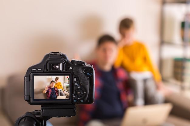 Rodzina vloggerów nagrywa filmy z mediów społecznościowych siedząc na kanapie