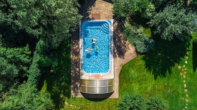 Rodzina w basenie widok z drona z lotu ptaka, szczęśliwa matka i dzieci pływają na nadmuchiwanych pierścieniowych pączkach i bawią się w wodzie na wakacjach rodzinnych, tropikalne wakacje w ośrodku