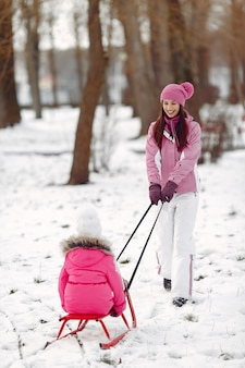 Rodzina w czapki zimowe z dzianiny na rodzinne wakacje świąteczne. kobieta i mała dziewczynka w parku. ludzie bawią się saniami.