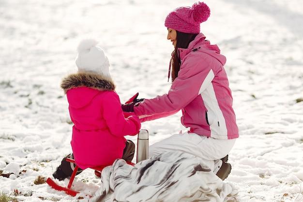 Rodzina w czapki zimowe z dzianiny na rodzinne wakacje świąteczne. kobieta i mała dziewczynka w parku. ludzie mają termos.