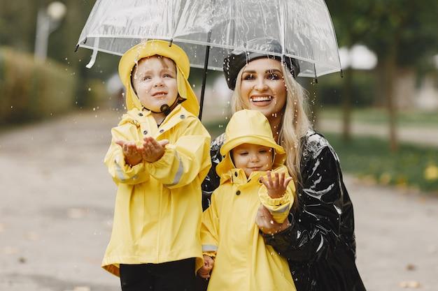 Rodzina w deszczowym parku. dzieci w żółtych płaszczach przeciwdeszczowych i kobieta w czarnym płaszczu.