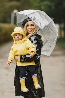 Rodzina w deszczowym parku. dzieciak w żółtym płaszczu przeciwdeszczowym i kobieta w czarnym płaszczu.