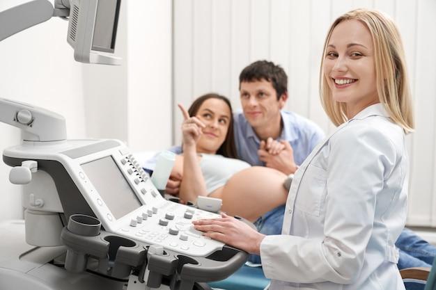 Rodzina w diagnostyce ultrasonograficznej, lekarz uśmiecha się, pozuje.