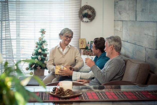 Rodzina w domu ciesząca się i świętująca noc bożego narodzenia wraz z prezentami i drobiazgami do tradycyjnej wymiany