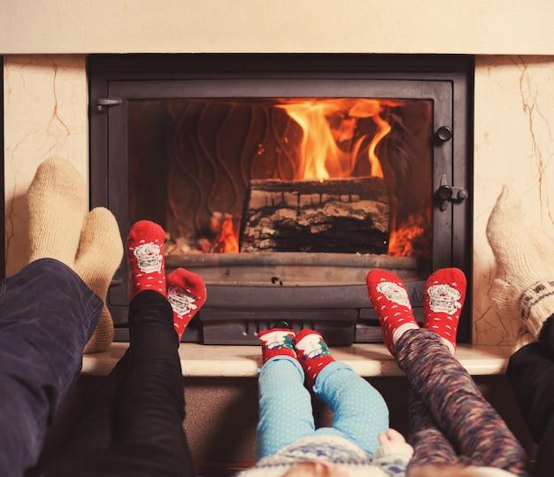 Rodzina w domu. stopy w skarpetkach przy kominku. koncepcja zimowych wakacji