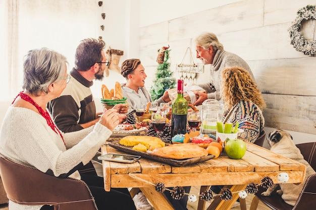 Rodzina w domu świętuje wigilijny obiad i daje sobie prezenty