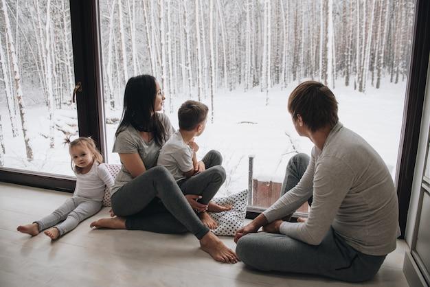 Rodzina w domu w piżamie. córka i syn. wstawać rano. przytulanie i całowanie, wyglądanie przez okno. piękna zima za oknem. duże okna na podłogę. ładny widok z okna.