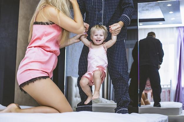 Rodzina w domu w sypialni mama, tata i dziecko są razem szczęśliwi o poranku